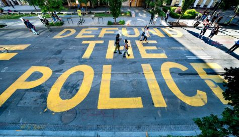 "Protesters in Washington write ""Defund the Police"" on the street."